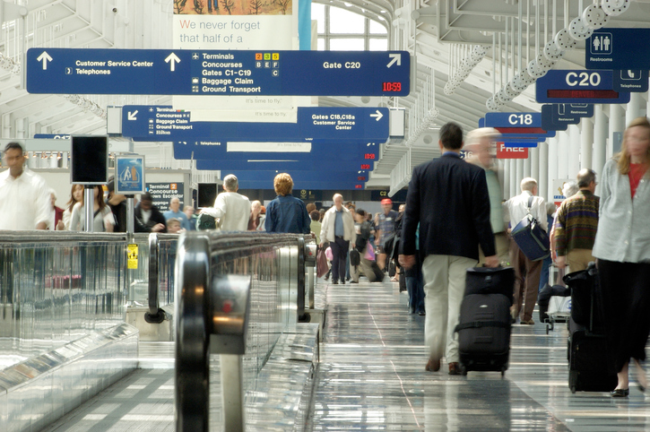 Busy airport and travellers finding terminals