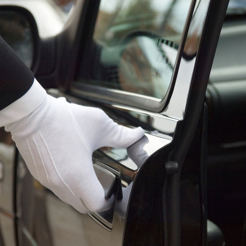 A white gloved hand of a uniformed doorman / chauffeur opening / closing a black car door.
