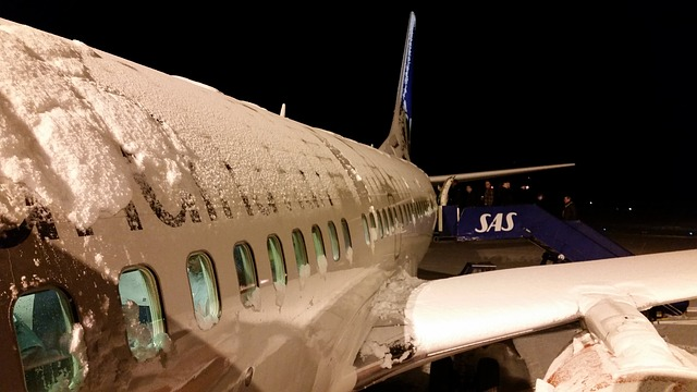 Airplane covered in snow on runway experiencing delays due to winter weather