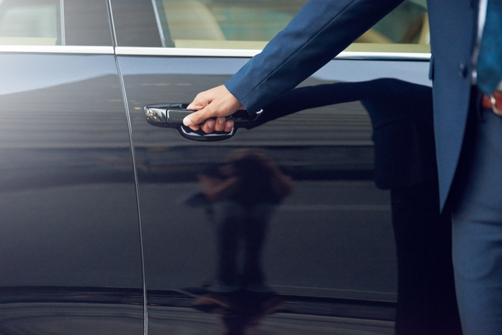 Private car service for business travellers - chauffeur opening car door