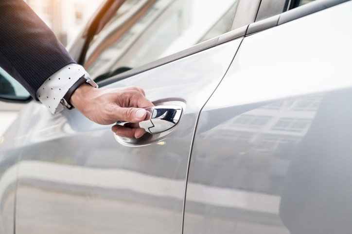 Chauffeur's hand on handle. Close-up of man in formal wear opening a passenger car door