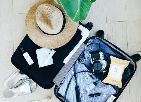 Suitcase with packed items for travel to the Hamptons - 2019 guide