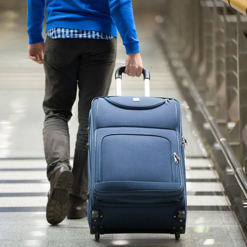 Man pulling suitcase through airport